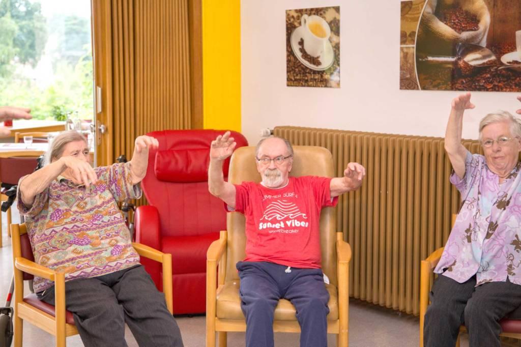 Lachende Bewohner bei der Bewegunstherapie
