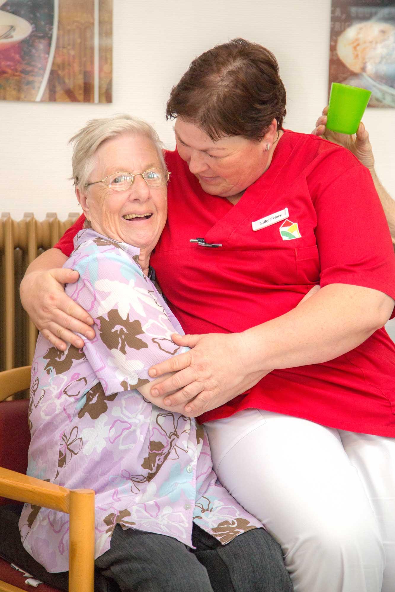 Lachende Bewohnerin und Pflegerin