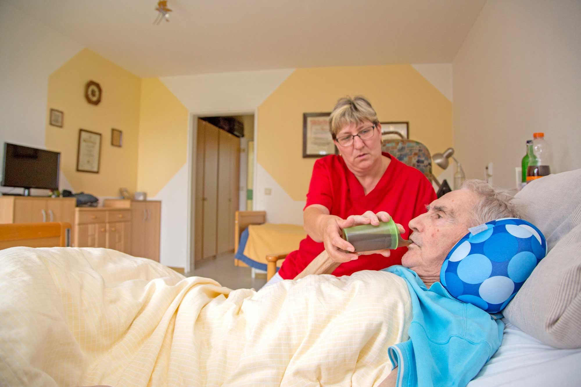 Pflegerin füttert einen bettlägerigen Bewohner