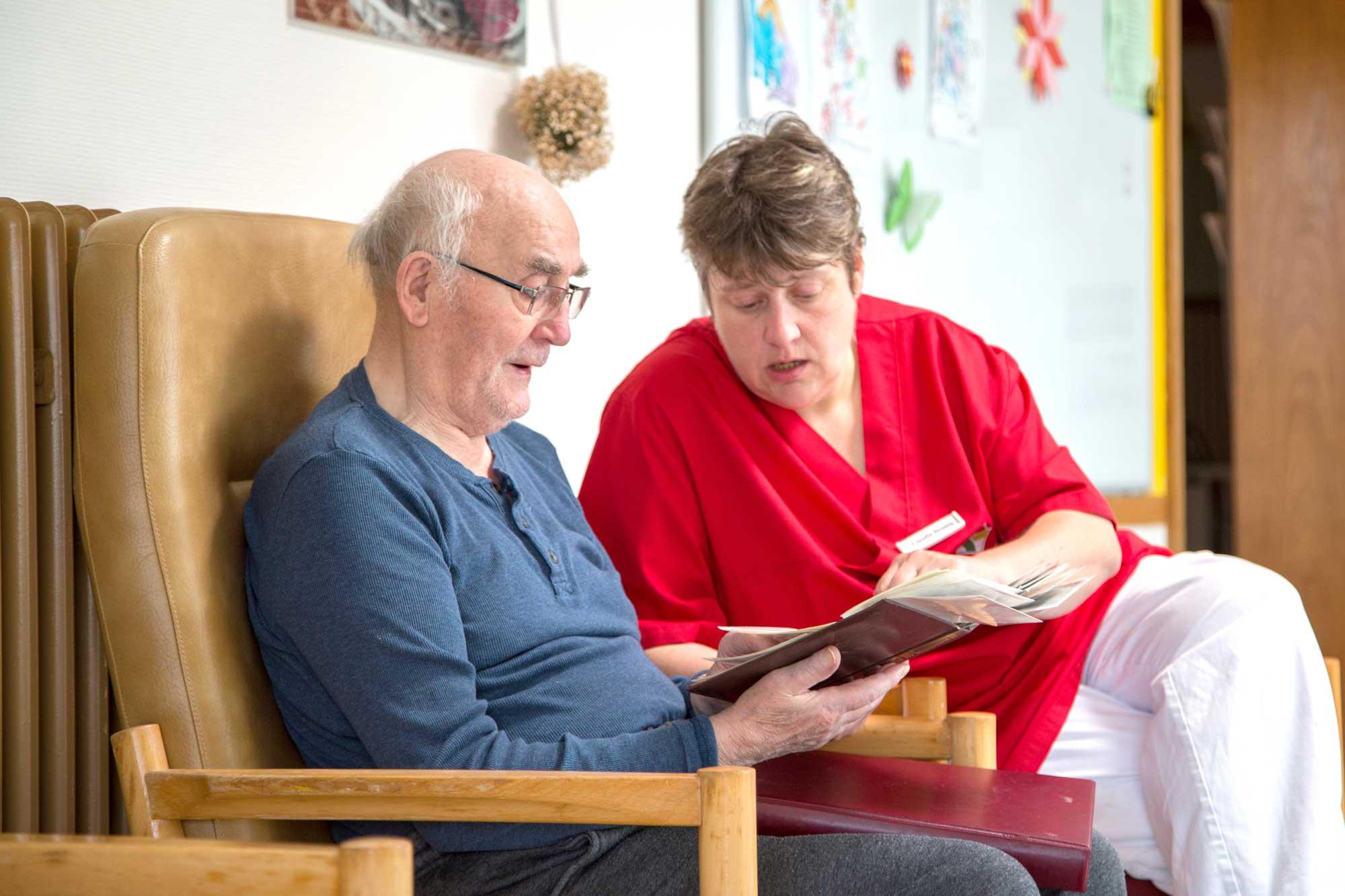 Pflegekraft mit Bewohner beim Fotos schauen